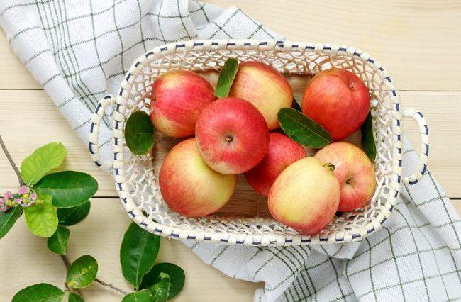 Корзина с яблоками на столе